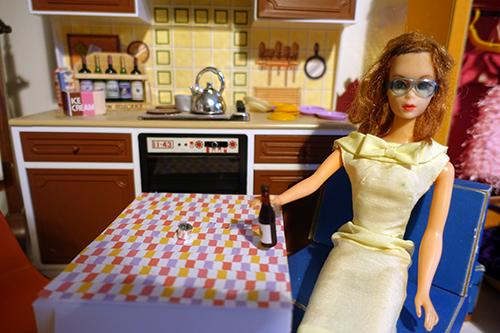 Lola med gul klänning och blå galärer och en halvflaska vin.